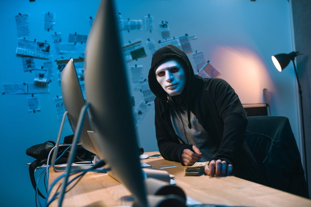 hooded hacker in mask with stack of money on desk